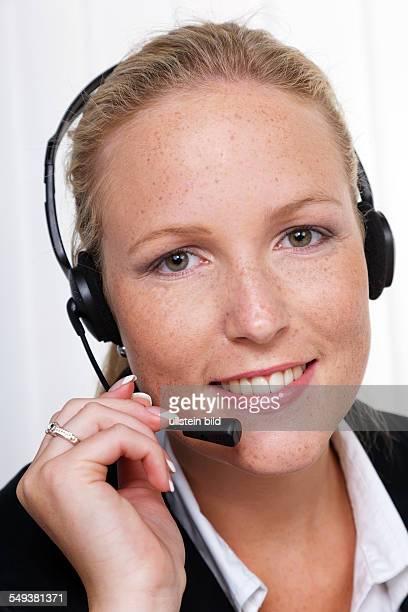 Eine freundliche junge Frau mit Headset im Kundendienst telefoniert mit einem Kunden