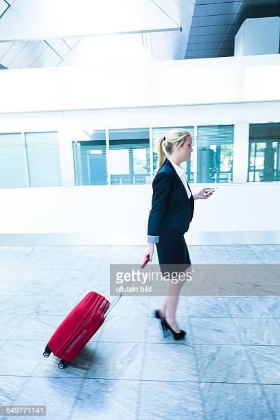 Eine Geschäftsfrau mit Koffer und Smartphone auf einem Flughafen Mobilität und Kommunikation bei Geschäftsreisen
