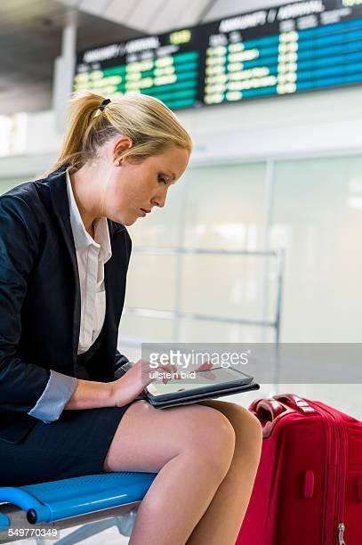 Eine Geschäftsfrau mit Koffer und Tablet Computer auf einem Flughafen Mobilität und Kommunikation bei Geschäftsreisen Roaming Gebühren im Ausland