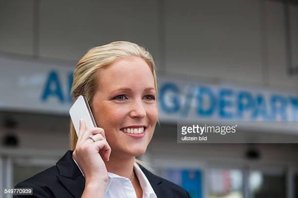 Eine Geschäftsfrau telefoniert mit ihrem Handy am Flughafen Roaminggebühren bei Smartphones im Ausland
