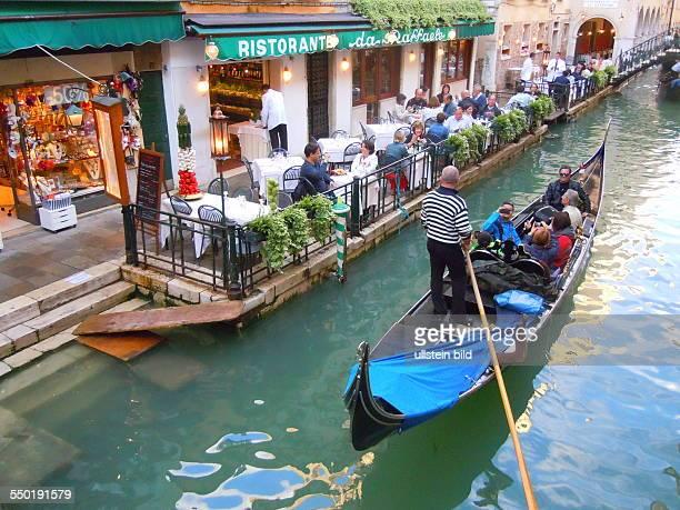 Eine Gondel mit Pasagieren fährt an einer RestaurantTerrasse im Stadtteil San Marco vorbei