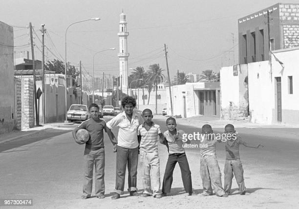 Eine Gruppe Kinder ein Junge hält einen Fußball imArm posieren in einer Straße mit einem Minarett im Hintergrund in Tripolis Hauptstadt von Libyen...