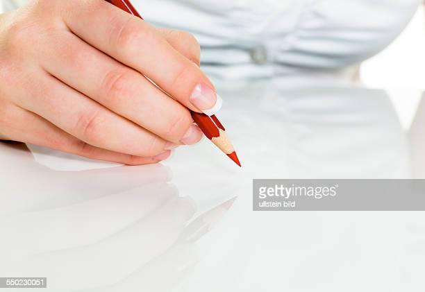 Eine Hand hält einen roten Stift Symbolfoto für Einsparungen und Budegt Kürzungen