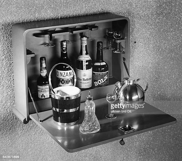 Eine hängende Hausbar mit Eisbehälter Eiszange Shaker in Kugelform und AngosturaträuflerModell von Küster und Perryveröffentlicht Dame 25/1937