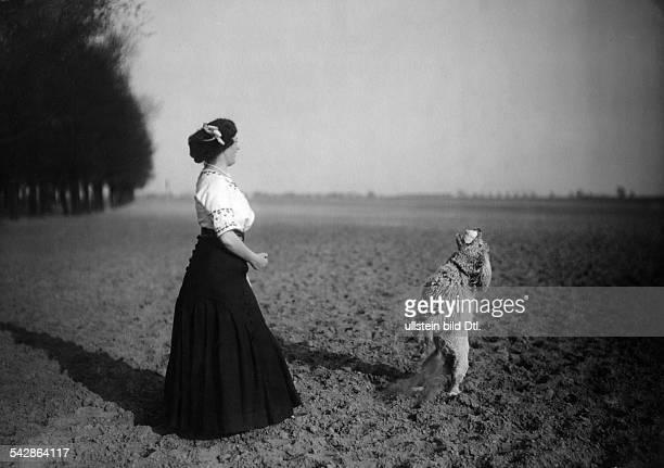 Eine Hundehalterin mit ihrem Pudel auf dem Feld der Hund fängt etwas auf undatiert vermutlich 1911Foto Conrad HünichBild ist Teil einer Serie