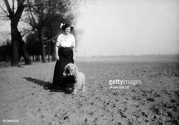Eine Hundehalterin mit ihrem Pudel auf dem Feld der Hund trägt die Handtasche der Frau undatiert vermutlich 1911Foto Conrad HünichBild ist Teil einer...