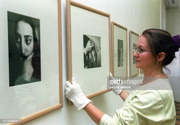 """Eine junge Dame hängt am 13.8.1999 im Frankfurter Leinwandhaus das Foto """"Hände und Brille von Paul Arma """" des Fotografen Andre Kertesz auf. Im..."""