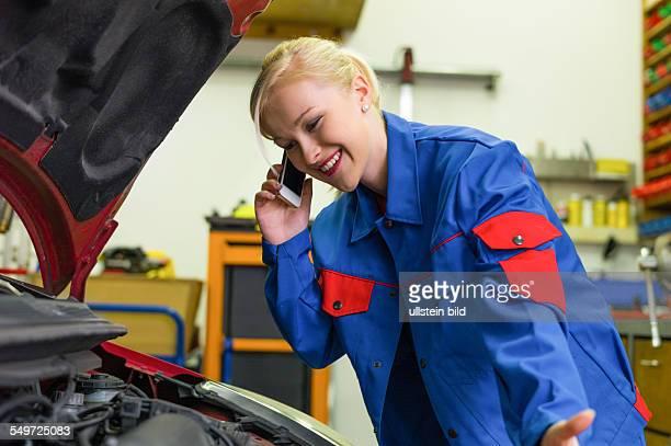 Eine junge Frau als Mechaniker in einer Autowerkstatt. Seltene Berufe für Frauen. Auto wird in Werkstatt repariert