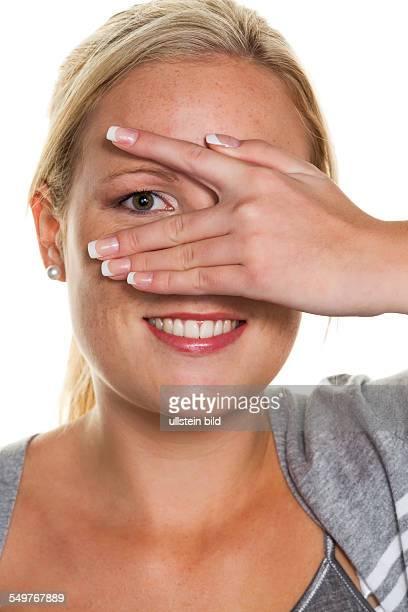 Eine junge Frau blickt durch die Finger ihrer Hand Symbolfoto für Durchblick und Flirt