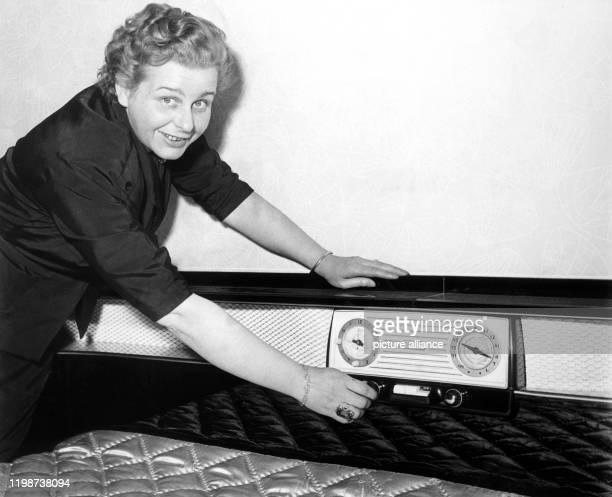 Eine junge Frau führt das eingebaute Weckradio im Kopfteil eines Französischen Bettes vor, aufgenommen im Januar 1956 anlässlich der Möbelmesse in...