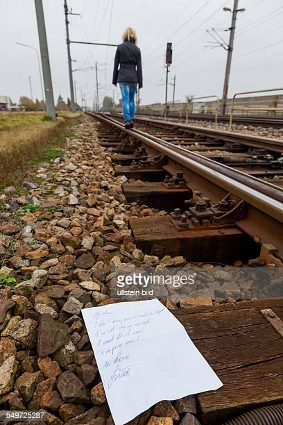 Eine junge Frau hinterlässt einen Abschiedsbrief und geht in Selbstmordabsicht auf einem Gleis Brief in englischer Sprache