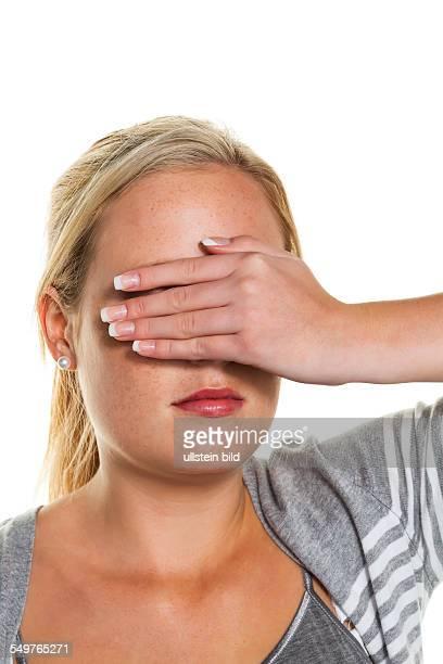 Eine junge Frau hält sich die Augen zu Symbolfoto für nicht sehen wollen und Verdrängung