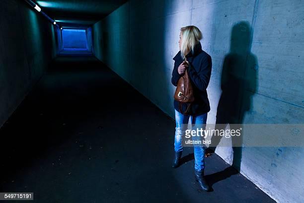 Eine junge Frau in einer Unterführung für Fußgänger hat Angst vor Belästigung und Kriminalität