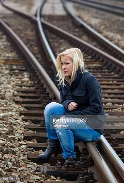Eine junge Frau ist traurig ängstlich und deprimiert Sitzt auf einem Gleis und ist einsam