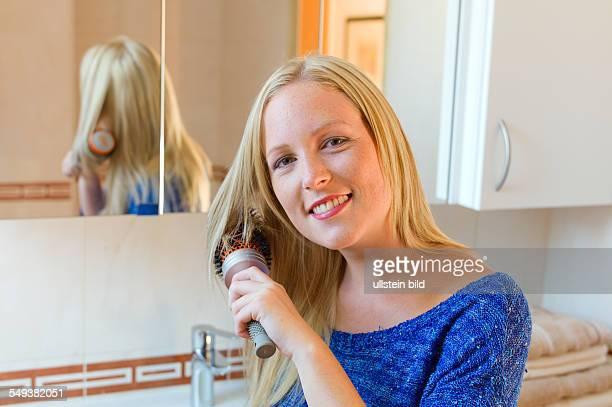 Eine junge Frau kennt sich mit einer Bürste ihre langen blonden Haare im Badezimmer