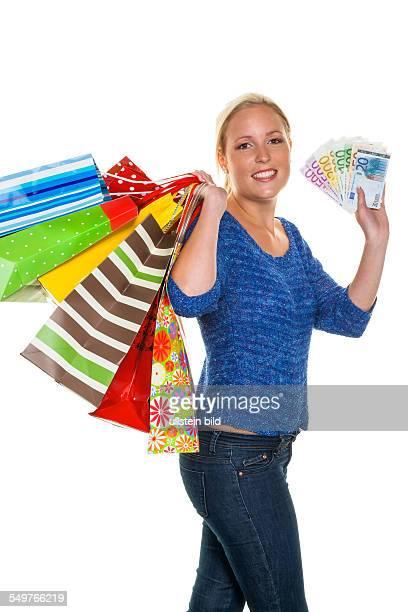 Eine junge Frau kommt mit vielen Einkaufstaschen vom Shopping zurück Mit Euro Geldscheinen