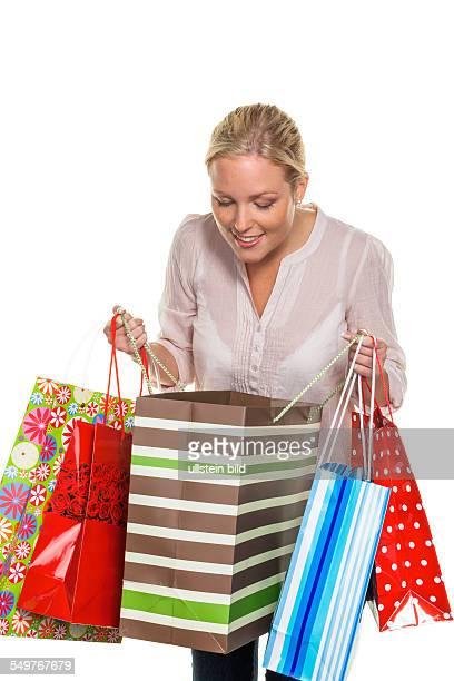 Eine junge Frau kommt mit vielen Einkaufstaschen vom Shopping zurück
