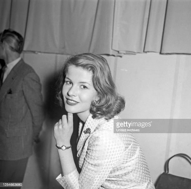 Eine junge Frau lächelt hinter der Bühne in die Kamera, Deutschland 1950er Jahre.