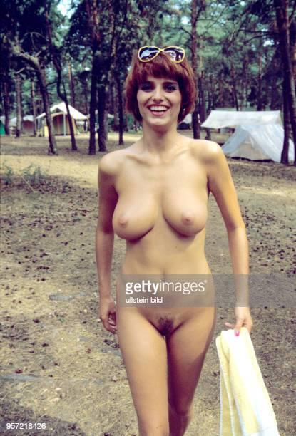 Eine junge Frau läuft hüllenlos über einen Zeltplatz am Zeesener See in SenzigWaldesruh wo versteckt in waldreicher Gegend das über 60 Jahre alte...