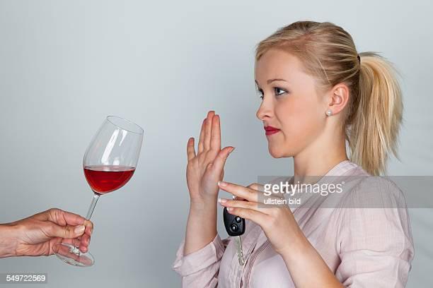 Eine junge Frau mit Autoschlüssel verweigert ein Glas Wein Don't drink and drive