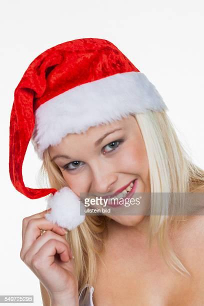 Eine junge Frau mit der Mütze eines Weihnachtsmannes Weihnachtsfrau zu Weihnachten vor weißem Hintergrund