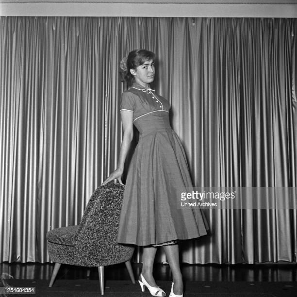 Eine junge Frau mit einem Cocktailsessel in einem Kleid Deutschland 1950er Jahre