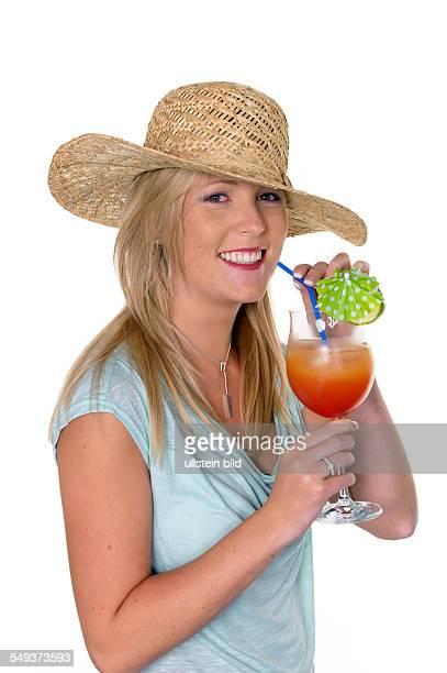 Eine junge Frau mit einem Sonnenhut trinkt einen Cocktail