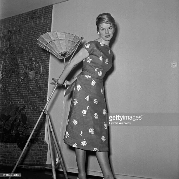 Eine junge Frau mit einer Deckenlampe in einem Kleid Deutschland 1950er Jahre