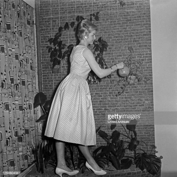 Eine junge Frau mit einer Gießkanne in einem Kleid Deutschland 1950er Jahre