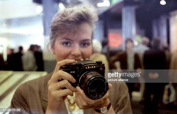 Eine junge Frau mit einer Kamera der Firma Leica auf der Photokina in Köln am .