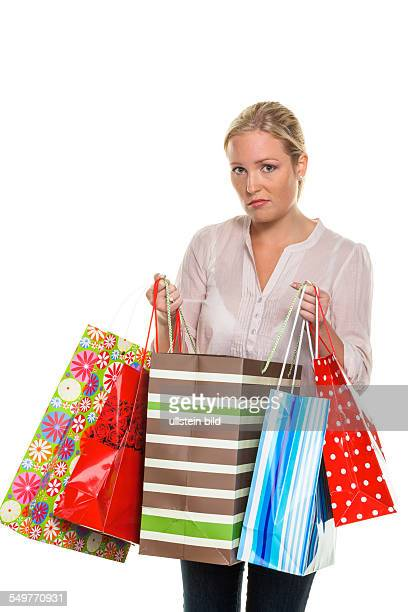 Eine junge Frau mit Einkaufstaschen kommt vom Shopping zurück Überschuldung Privatkonkurs oder Warenumtausch