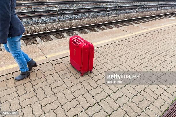 Eine junge Frau mit Koffer wartet auf dem Bahnsteig eines Bahnhofes auf ihren Zug Einsame Gepäckstücke auf Bahnhöfen sind gefährlich