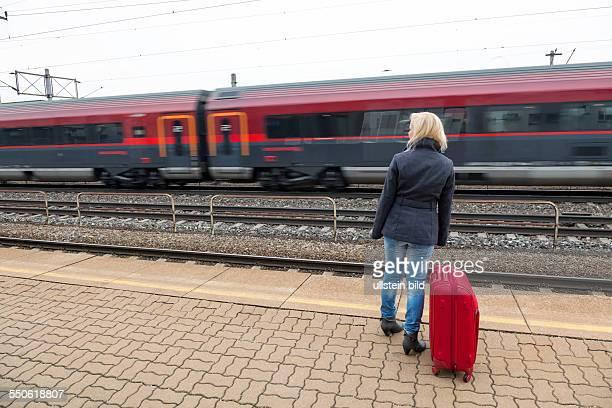 Eine junge Frau mit Koffer wartet auf dem Bahnsteig eines Bahnhofes auf ihren Zug Zugverspätungen