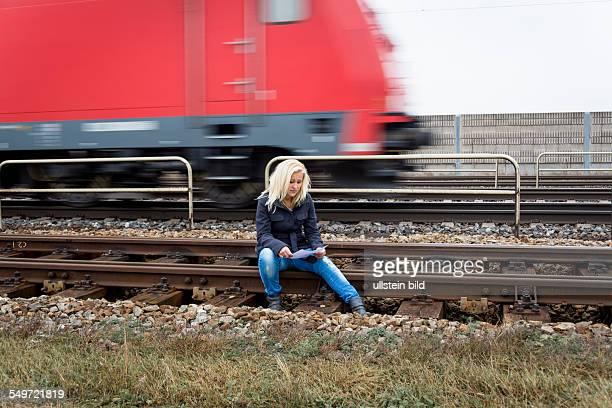Eine junge Frau mit Selbstmord Gedanken sitzt auf einem Gleis Hält Abschiedsbrief in der Hand und denkt über ihren Suizid nach