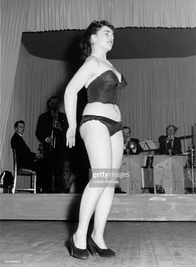 Eine junge Frau präsentiert auf der Bühne in einem