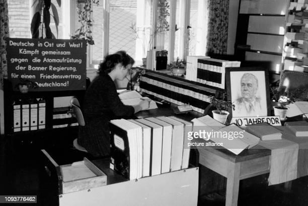 """Eine junge Frau sitzt in einer Bibliothek der Universität Jena die mit einer Losung """" Deutsche in Ost und West! Kämpft gemeinsam gegen die..."""