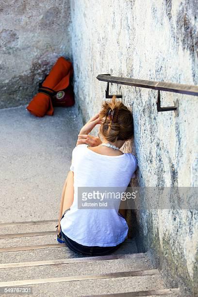 Eine junge Frau sitzt traurig und einsam auf einer Treppe