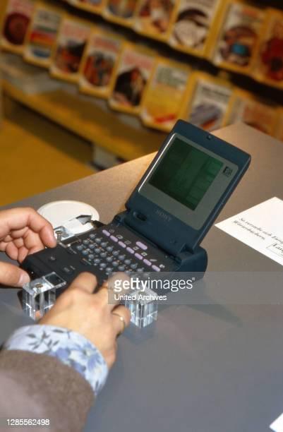 Eine junge Frau testet eine Handheld-Datenbank auf der Buchmesse in Frankfurt, Deutschland 1993.