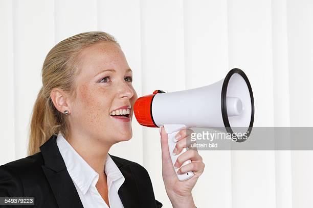 Eine junge Geschäftsfrau mit einem Megaphon macht eine Durchsage