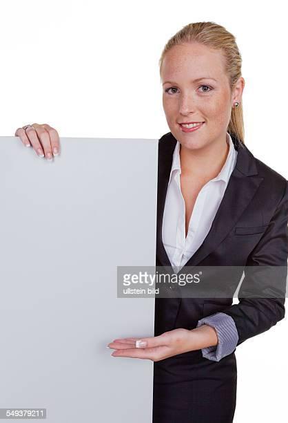 Eine junge hübsche Frau in Business Kleidung mit einer leeren Werbetafel