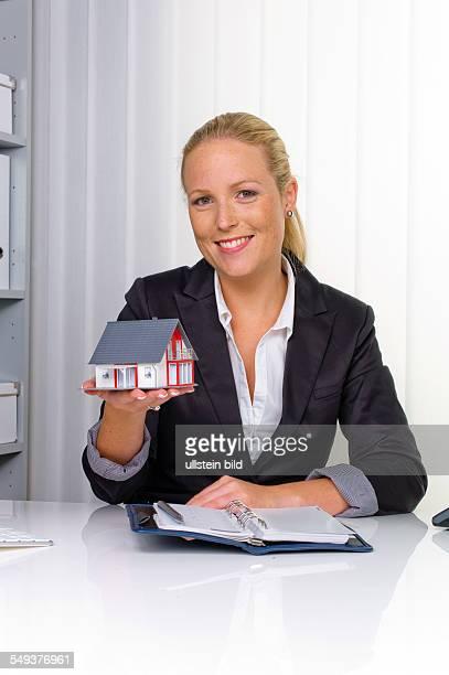 Eine junge Immobilien Maklerin mit einem Modellhaus in ihrem Büro