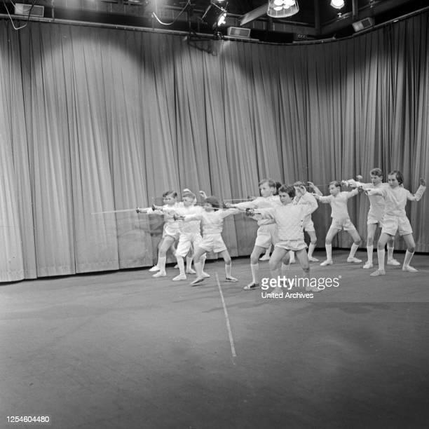 Eine Kindergruppe einer Fechtschule auf der Bühne beim Training, Deutschland 1950er Jahre.