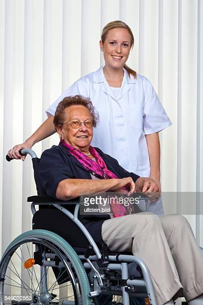 Eine Krankenpflegerin und eine alte Frau im Rollstuhl