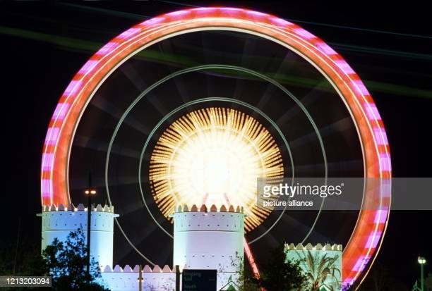 Eine Langzeitbelichtung lässt am die Konturen des Riesenrades auf der Expo in Hannover verschwimmen. Das farbig illuminierte Rad überragt das...