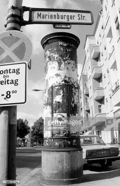 Eine Litfaßsäule mit abgerissenen Plakaten, aufgeommen im Juni 1990 in Ostberlin an der Marienburger Straße im Stadtbezirk Prenzlauer Berg. Ein...