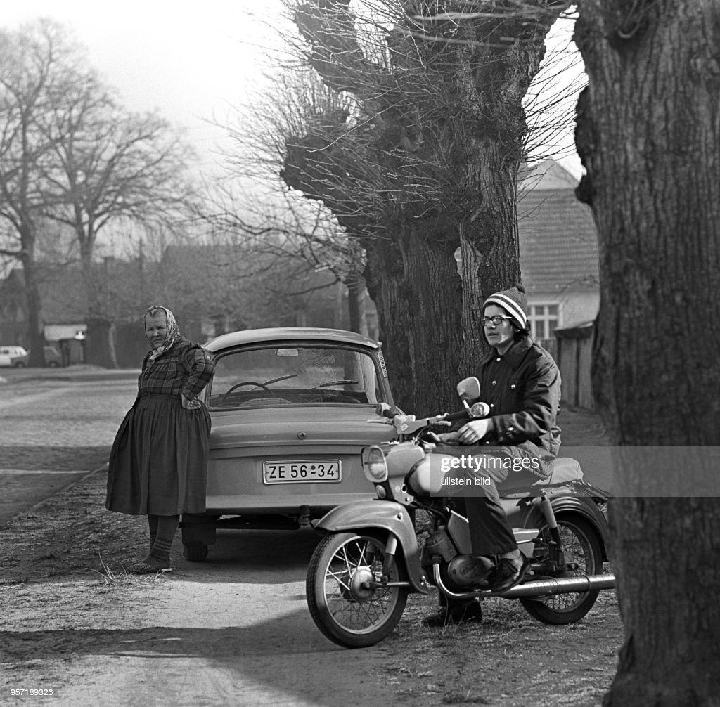 Eine ältere Frau in Tracht steht an einem Trabant und ein