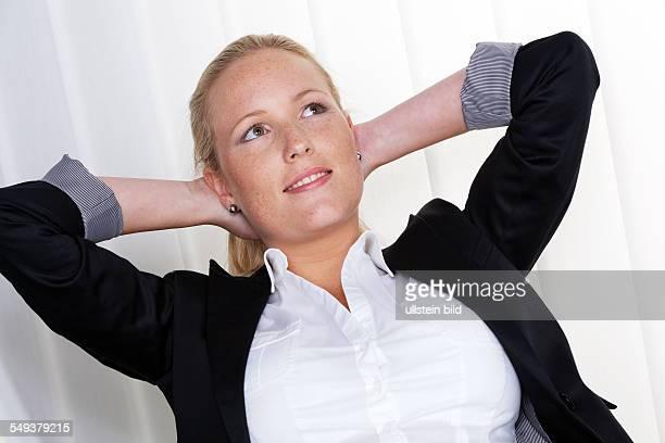 Eine nachdenkliche Geschäftsfrau sitzt auf ihrem Sessel und hat die Hände im Nacken verschränkt