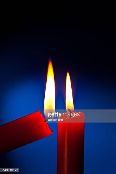 Eine rote Kerze wird mit einem Streichholz angezündet