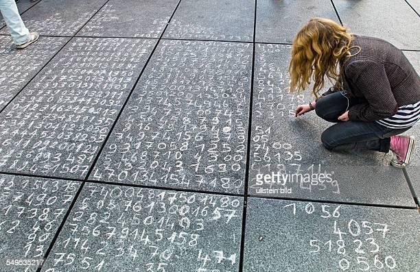 Eine Schülerin hat eine Rechenaufgabe auf ein Strassenpflaster geschrieben