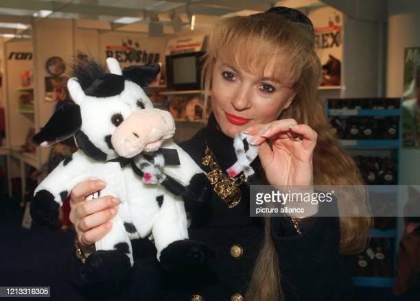 """Eine schwarz-weiße Plüsch-Kuh namens """"Mäggie"""" wirbt am 29.1.1997 auf der Nürnberger Spielwarenmesse mit der """"Original BSE-Schleife"""" um Solidarität..."""